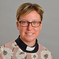 Kvinna med blommig skjorta och svart prästskjorta under