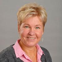 Kvinna med rosa skjorta och grå kofta