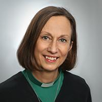 Kvinna med grön diakonskjorta.