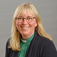 Kvinna med grön diakonskjorta och mörkblå kofta