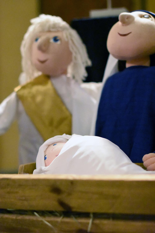 Lähikuva Jeesuslapsesta nukkemuodossa. Taustalla enkeli ja Maria.
